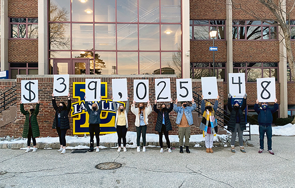 """Students hold signs spelling out """"$39,025.48"""""""