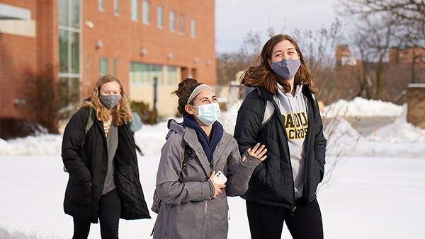 Students walking across a snow-covered campus