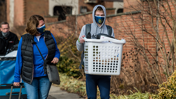 A student walking with parent holding laundry basket to move-into La Salle