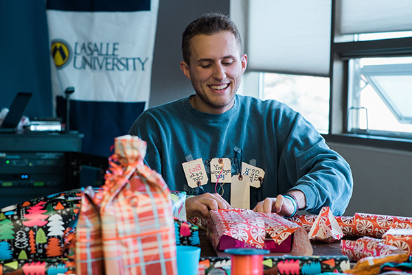 Student wrapping Christmas gifts