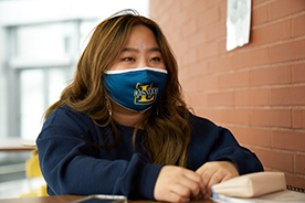 Female student studying with mask on