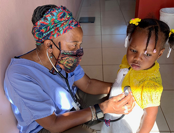 Dr. Hazell listening to heart rate of young girl while on a mission trip in Haiti